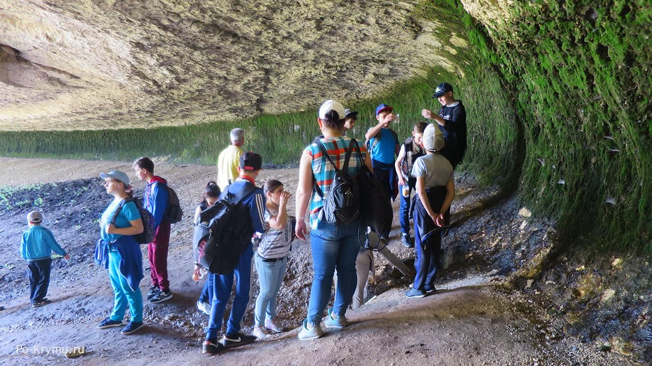 Туристы ловят капли воды, падающие с потолка пещеры.